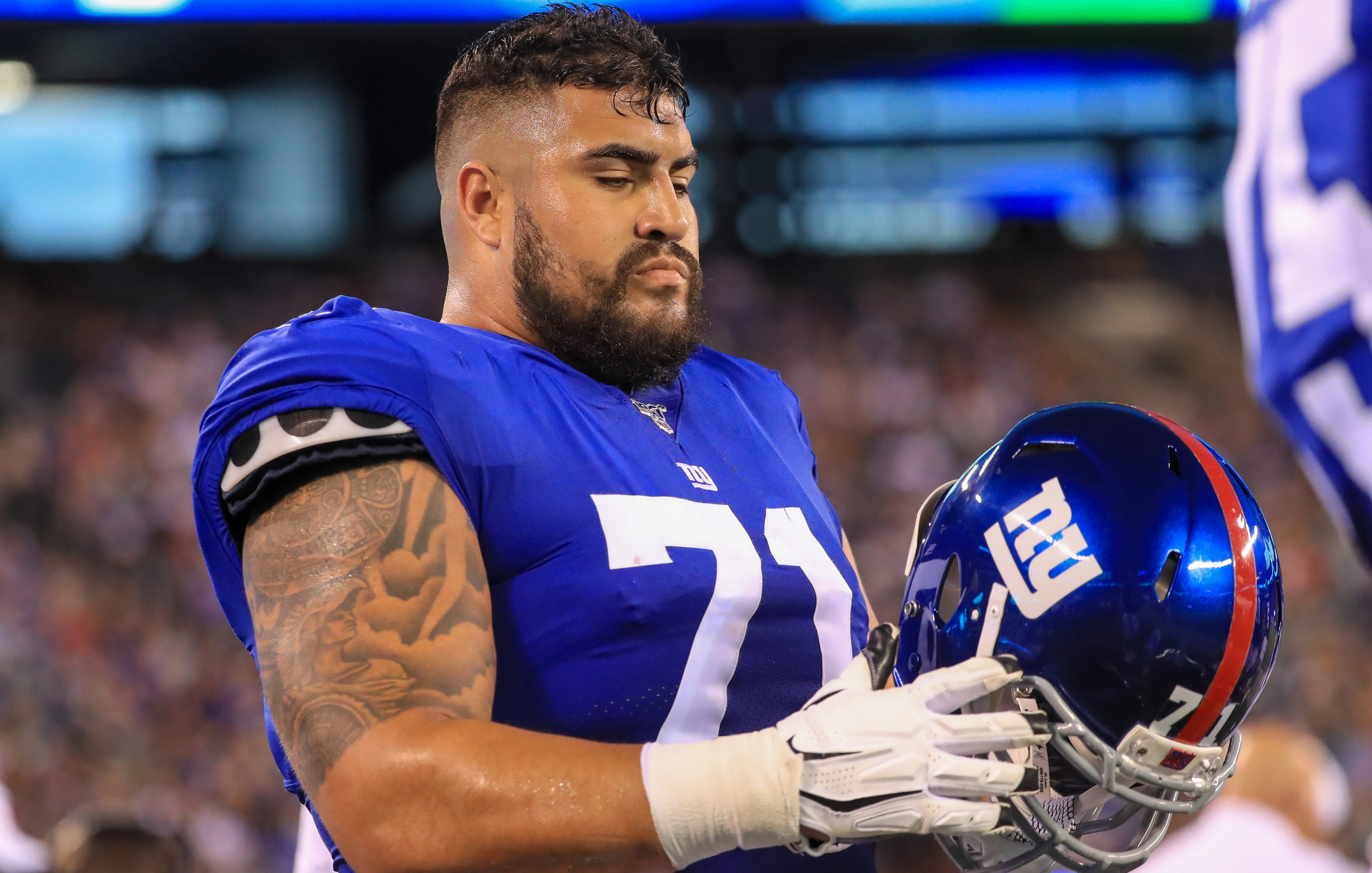 New York Giants guard Will Hernandez checking out his helmet during a game.