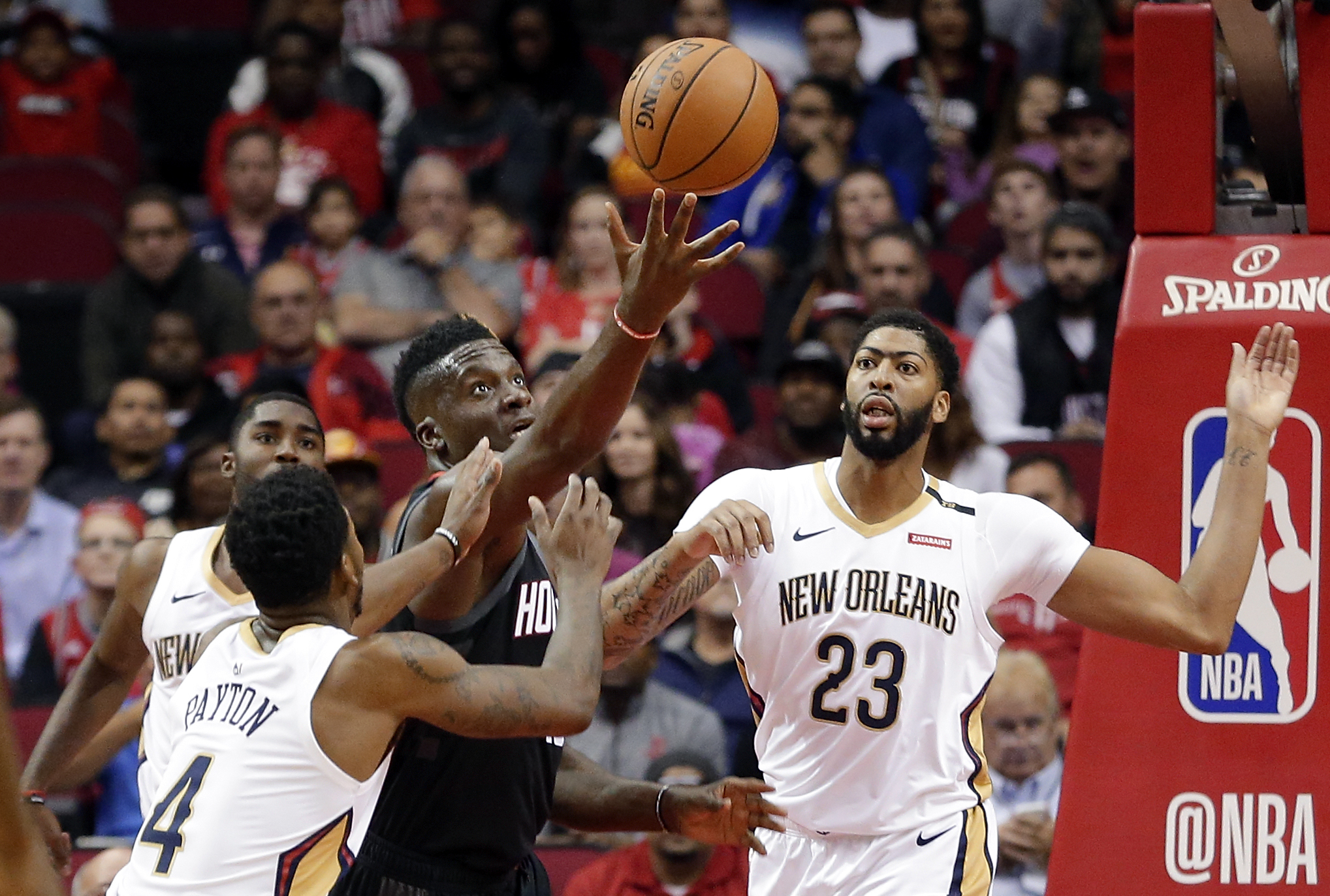 Houston Rockets center Clint Capela, center, reaches for a rebound between New Orleans Pelicans guard Elfrid Payton (4) and forward Anthony Davis (23) during the first half of an NBA basketball game Wednesday, Oct. 17, 2018, in Houston. (AP Photo/Michael Wyke) AP