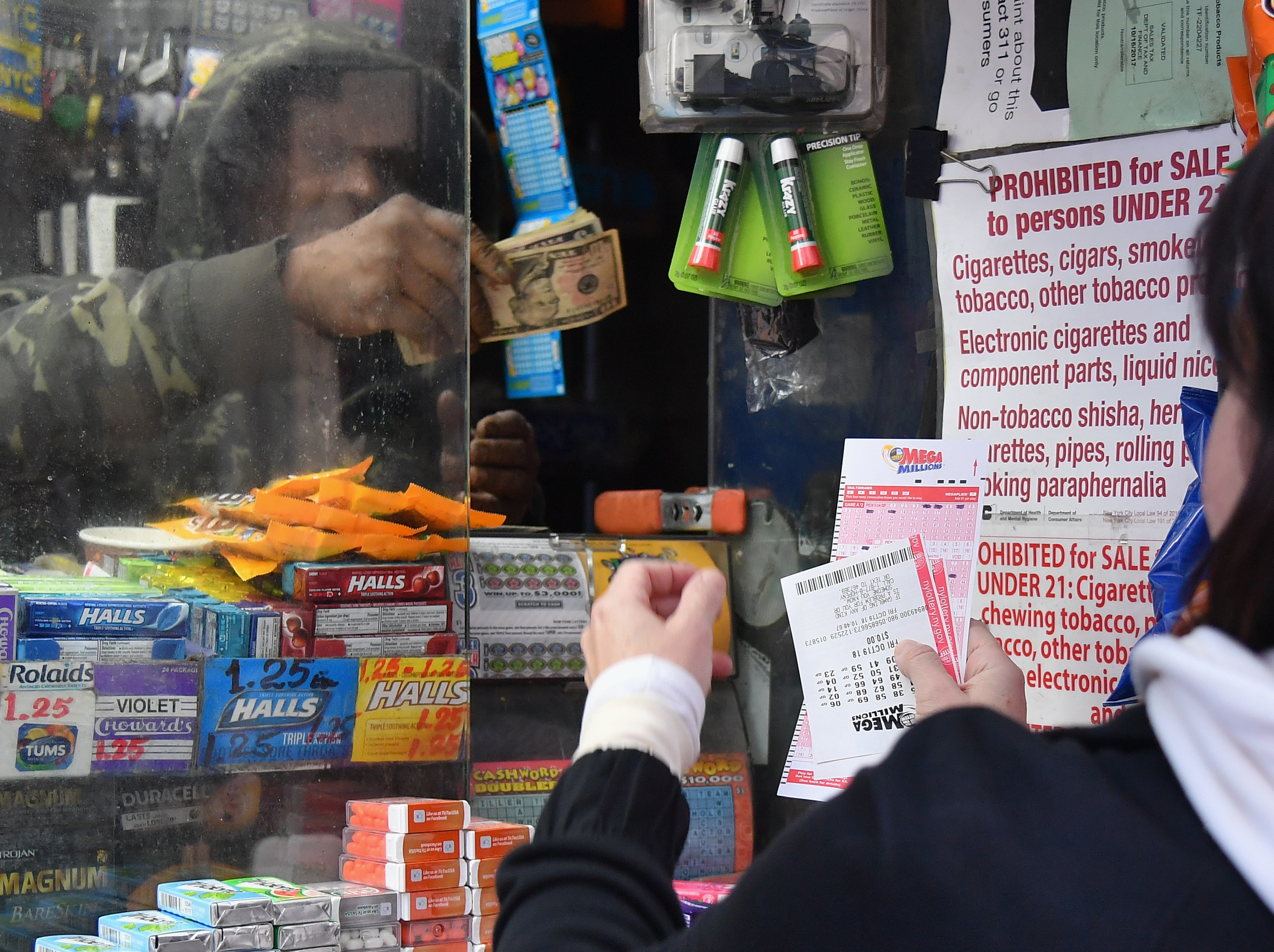 A woman purchases Mega Millions lottery tickets in New York City Friday, Oct. 19, 2018. The Mega Millions jackpot climbed from $970 million to $1 billion. (Angela Weiss/AFP/Getty Images)