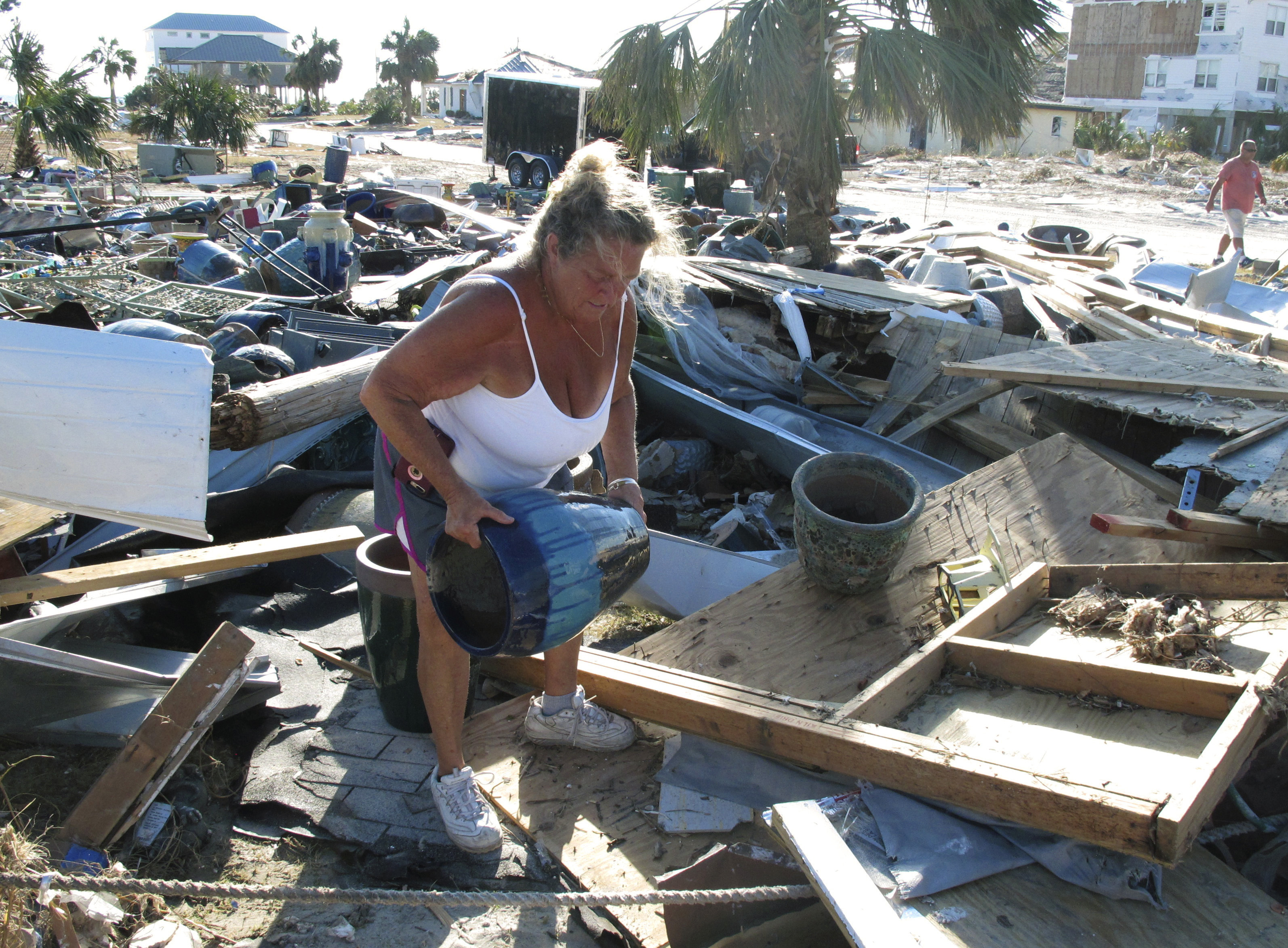 """In this Oct. 14, 2018 photo Dena Frost salvages an unbroken clay pot from the wreckage of her pottery business in Mexico Beach, Fla. For decades, the town has persisted as a stubbornly middlebrow enclave on what residents proudly refer to as Florida's """"Forgotten Coast."""" Businesses are locally owned. While some locals owned posh homes that overlooked the beach on stilts, many lived in mobile homes. (AP Photo/Russ Bynum)"""