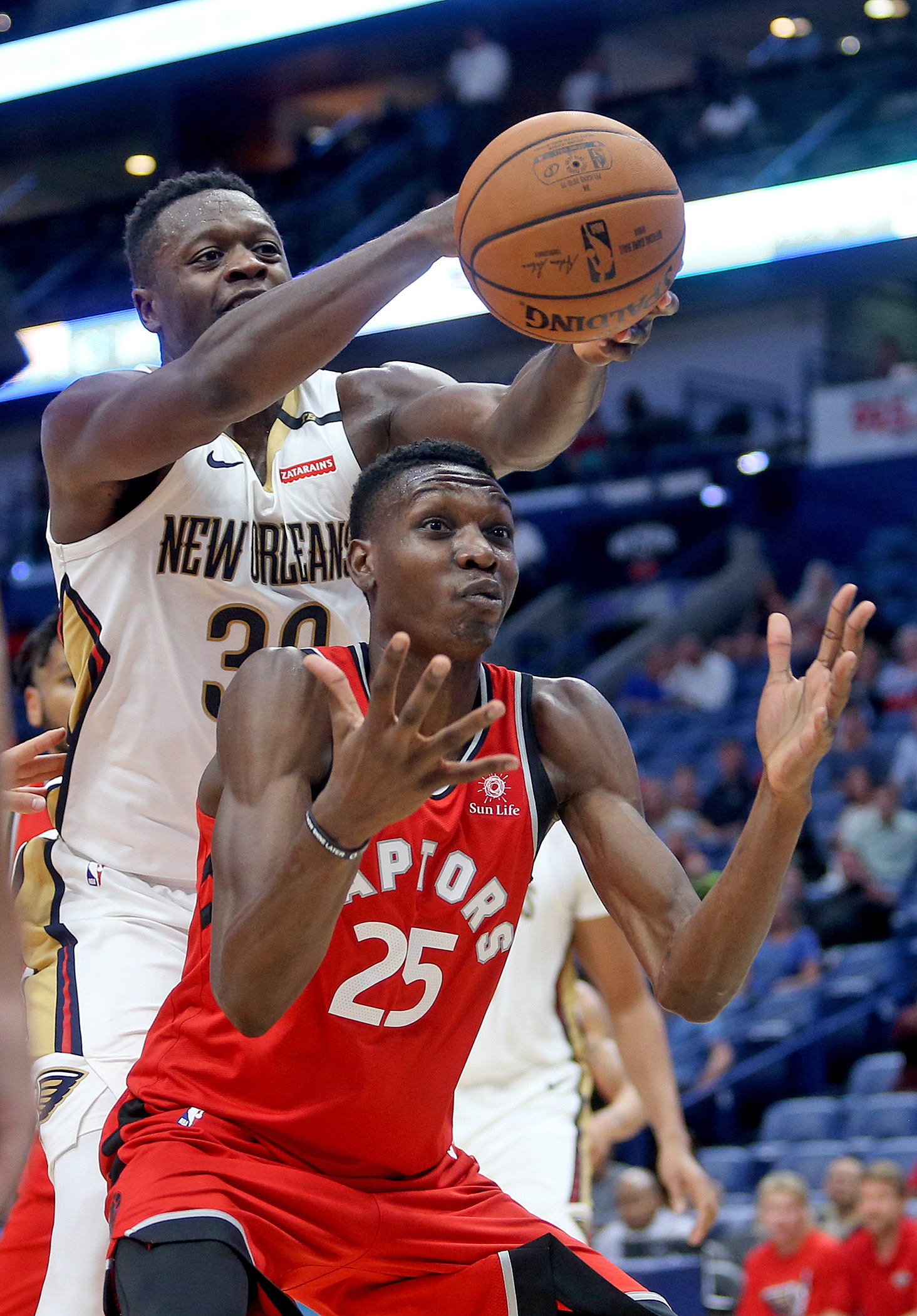 New Orleans Pelicans forward Julius Randle (30) takes a rebound away from Toronto Raptors forward Chris Boucher (25) during the preseason game between the Toronto Raptors and New Orleans Pelicans at the Smoothie King Center on Thursday, October 11, 2018. (Photo by Michael DeMocker, NOLA.com | The Times-Picayune)