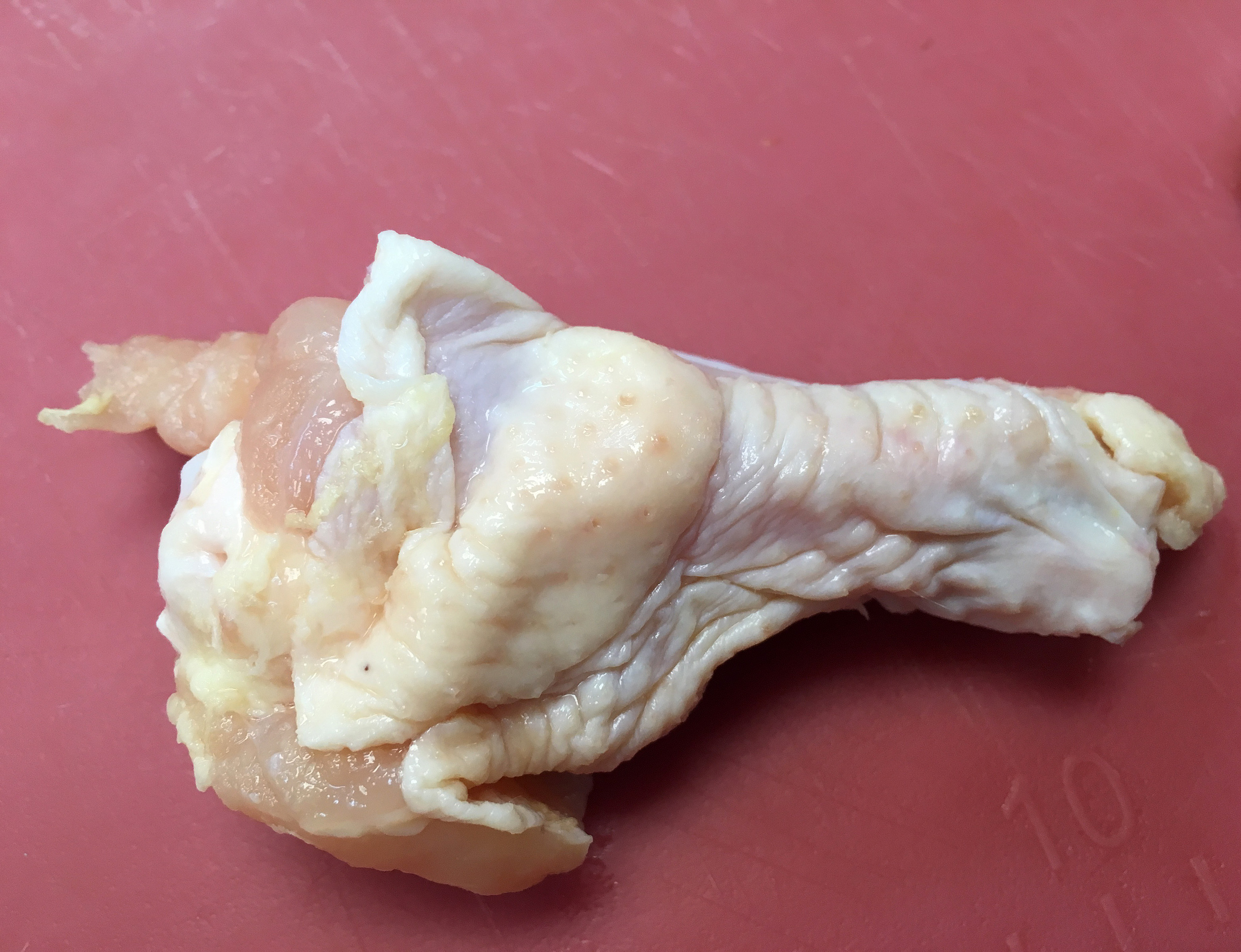 A raw chicken drumette.
