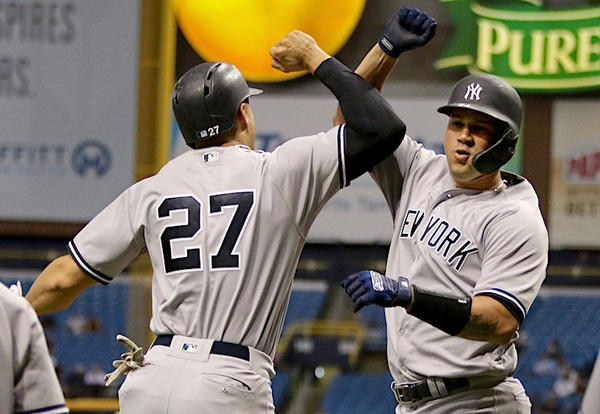 Yankees catcher Gary Sanchez (right) arms bumps designated hitter Giancarlo Stanton after hitting a three-run home run in the third inning against the Tampa Bay Rays at Tropicana Field on Tuesday night.