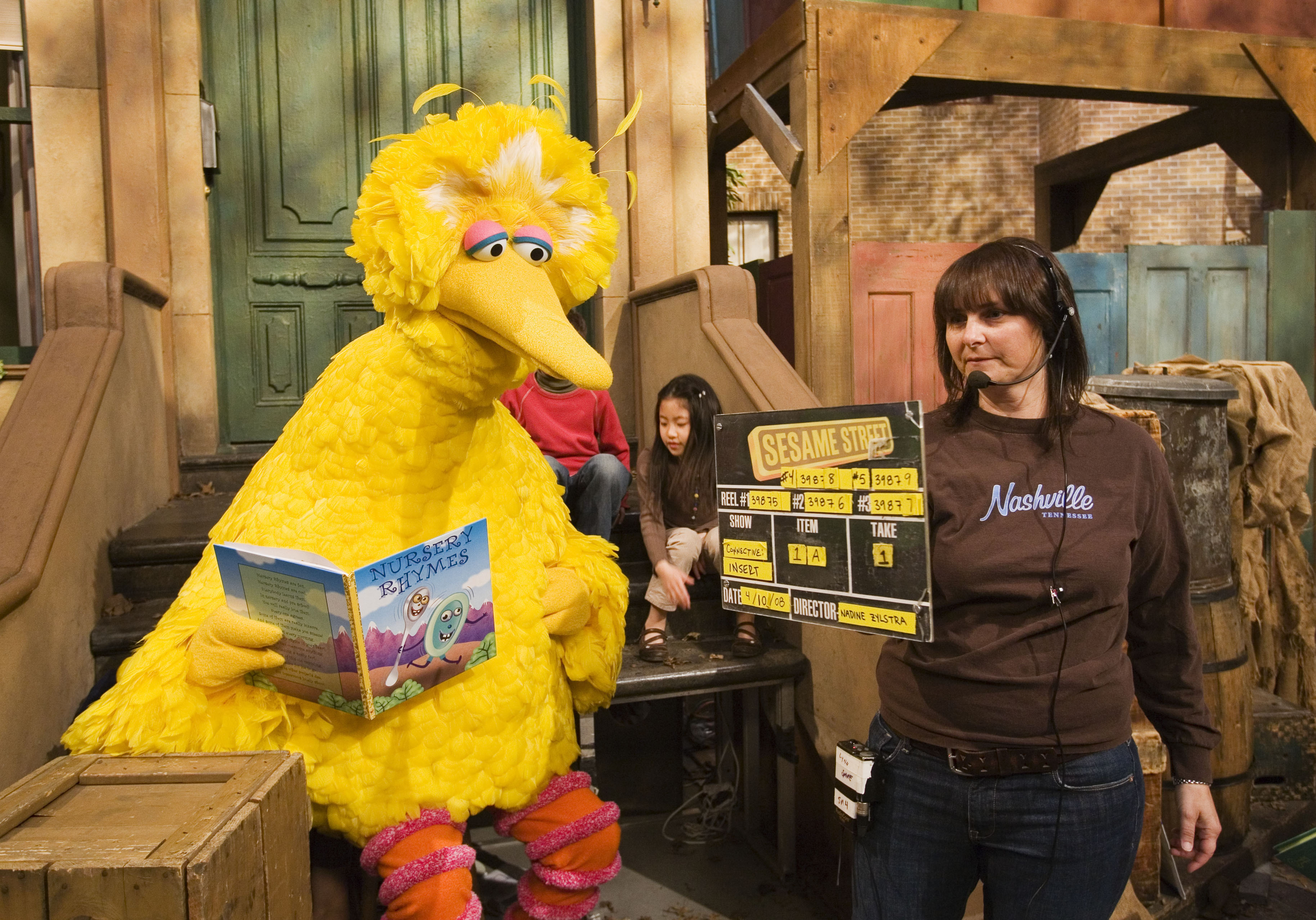 "In this April 10, 2008, file photo Lynn Finkel, stage manager for ""Sesame Street,"" slates a taping with Big Bird in New York. The puppeteer who has played Big Bird on ""Sesame Street"" is retiring after nearly 50 years on the show. (AP Photo/Mark Lennihan, File)"