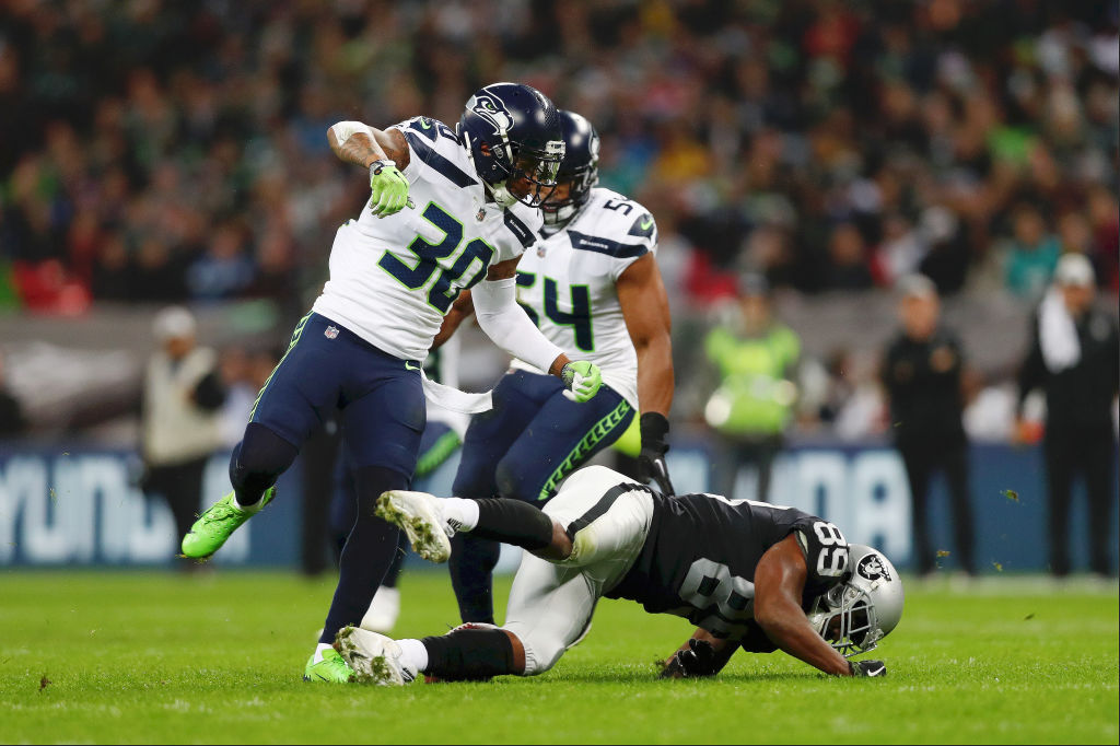 Oakland Raiders wide receiver Amari Cooper goes down after getting hit by Seattle Seahawks safety Bradley McDougald during an NFL game on Sunday, Oct. 14, 2018, in London.