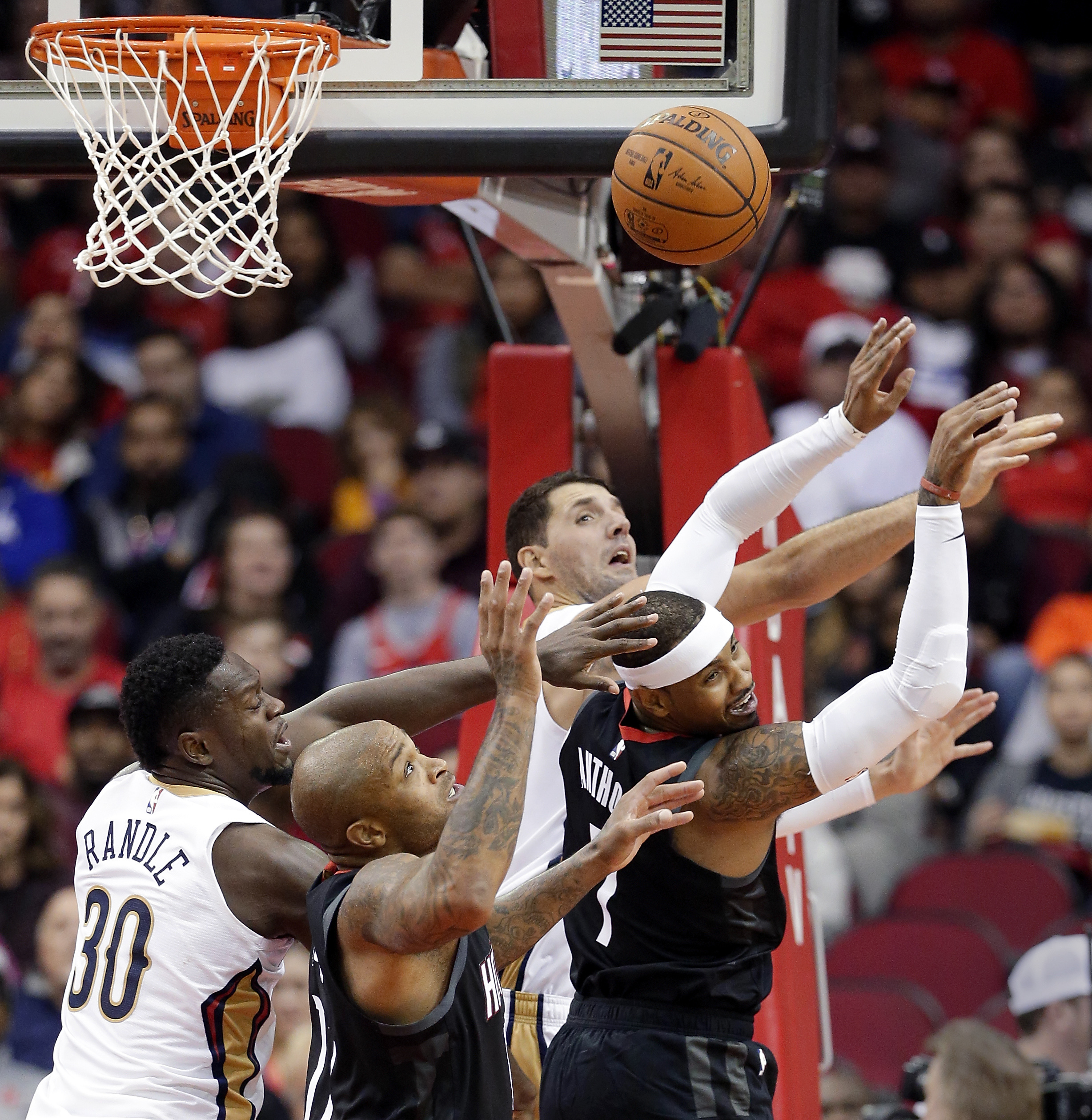 New Orleans Pelicans forward Julius Randle (30) and forward Nikola Mirotic (3) battle for a rebound with Houston Rockets forward PJ Tucker and Carmelo Anthony (7) during the second half of an NBA basketball game Wednesday, Oct. 17, 2018, in Houston. (AP Photo/Michael Wyke) AP