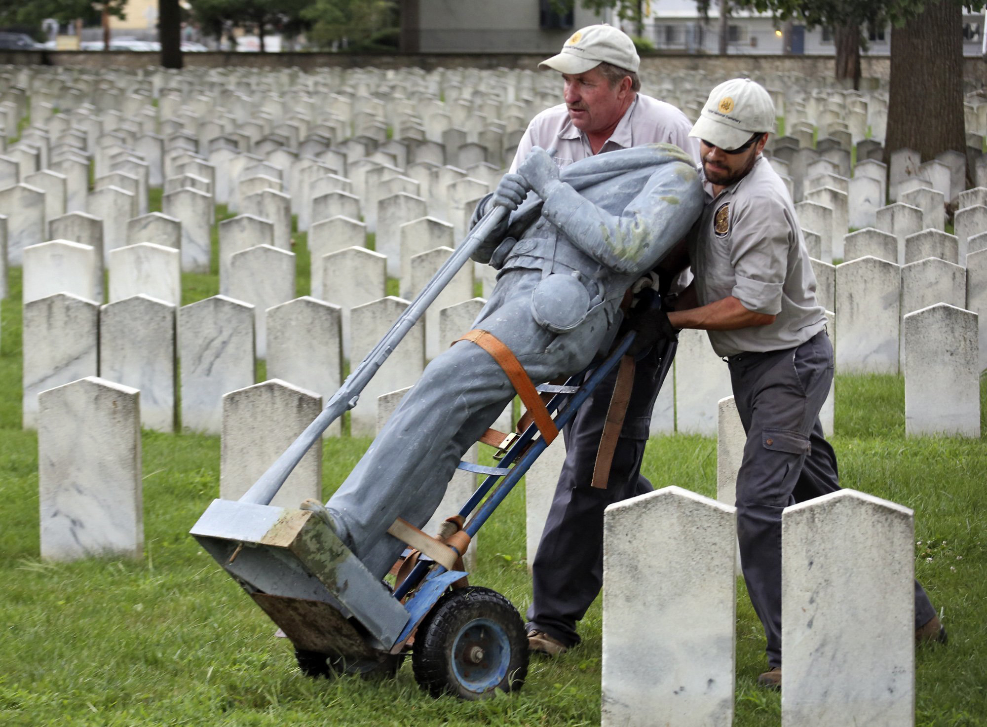 In this Aug. 22, 2017, photo, Bert Cambron, left, and Mark Wilson, employees of Dayton National Cemetery, move the vandalized Civil War Confederate soldier statue that stood in Camp Chase Confederate Cemetery in Columbus, Ohio. Two days later, the VA contracted with the Westmoreland Protection Agency, based in Sunrise, Fla., to provide unarmed security guards at Camp Chase and two other cemeteries. After last year's deadly clash between white nationalists and counter-protesters in Charlottesville, Va., the federal government quietly spent millions of dollars to hire private security guards to stand watch over several Confederate cemeteries, documents from the Department of Veterans Affairs show. (Eric Albrecht/The Columbus Dispatch via AP)